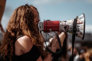 Woman speaking loudly through a megaphone