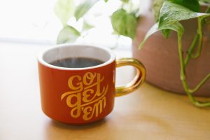 Cup of steaming coffee with the words Go Get Em on the outside