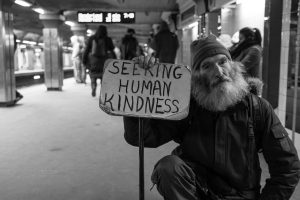 "Man holding sign that says, ""Seeking human kindness"""