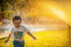 Happy kid running in sprinklers