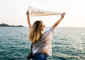 Woman holding freedom sign in front of ocean