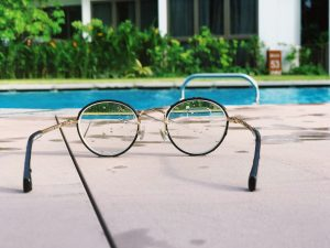 Reading glasses next to a pool